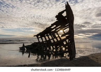 The skeleton of the Peter Iredale shipwreck at sunset in Oregon.