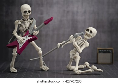 A skeleton playing electric guitar with a singer skeleton singing