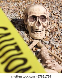Skeleton in rocks surrounded by yellow caution tape.