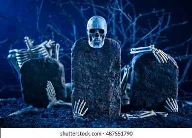 skeleton are scatter on the tombstone in the night time graveyard