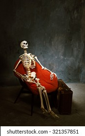 skeleton sit at the red armchair and wait