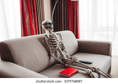 Skeleton sitting between book and remote control