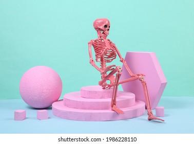 Skeleton sitting on podium with pink geometric shapas. Concept art. Minimalism halloween concept