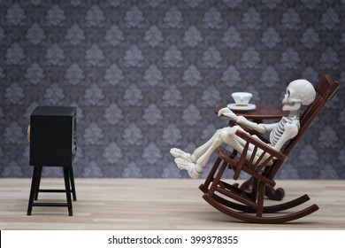 A skeleton sitting on rocking chair watching TV