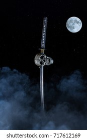 Skeleton Skull On Sword with Fog / Dark foggy night scene showing a katana sword through a skeleton skull stuck in the ground with moon and stars in the background.