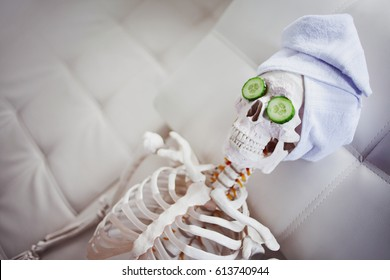 Skeleton in Spa salon with towel on her head and mask on her face, relaxes, care themselves. An absurd concept, social parody. Take care of beauty and forget about inner peace