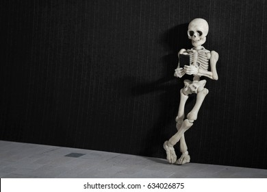 Skeleton standing with a smartphone in his hand