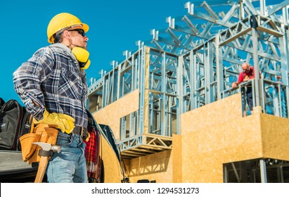 Skeleton Steel House Building. Construction Business Concept. Caucasian Worker in Yellow Hard Hat Taking Short Break During Working Hours.