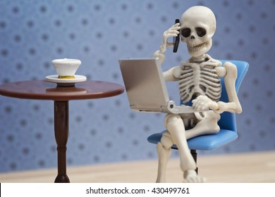 Skeleton working with smartphone and laptop