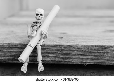 Skeletons with cigarette sit on wood table , selective focus