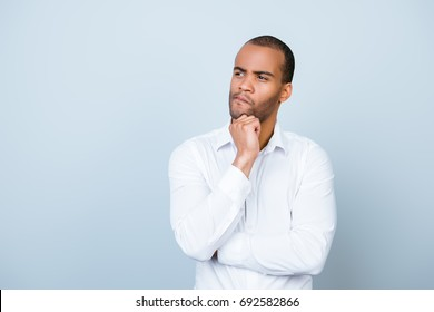 Skeptic, unsure, uncertain, doubts concept. Young african guy in formal wear is looking sceptical, has a grimace of distrust on light blue background