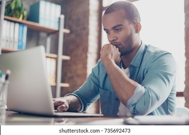 Skeptic young afro freelancer is making decision sitting at the office in casual smart, analyzing the data in the computer