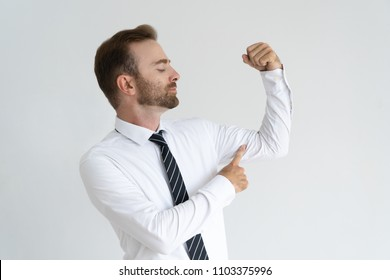 Skeptical business leader showing physical strength. Fair haired young man in tie flexing hand muscles and pointing at little bicep. Lack of fitness and mental labor concept