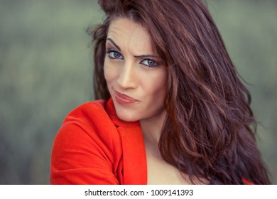 Skeptical. Closeup confused skeptical woman, having doubt, looking at you camera, isolated green background with copy space. Outdoors portrait