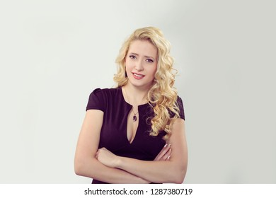 Skeptical. Closeup portrait confused skeptical shy timid woman looking at you camera.  Caucasian Business person in black formal dress, long blond curly hair isolated light grey gray studio background