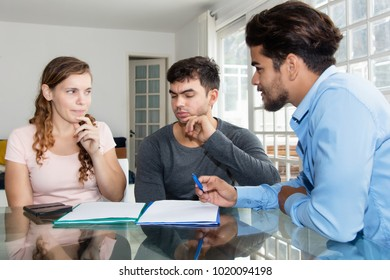 Skeptical couple with insurance contract and agent