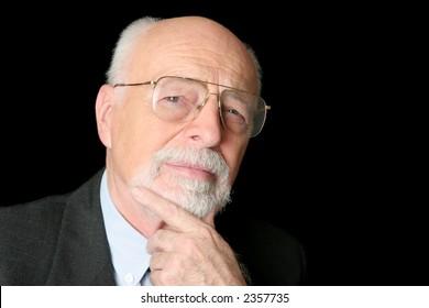 A skeptical looking, intelligent senior man over a black background.