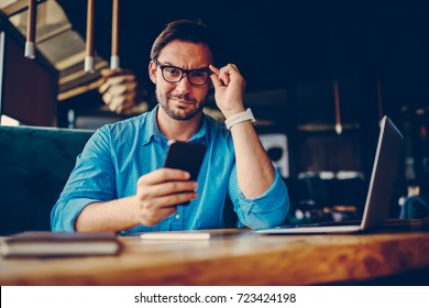 Skeptical male entrepreneur doubting in information from social networks browsing web site on mobile, portrait of proud CEO looking through eyeglasses skeptically confident in his opinion and ideas