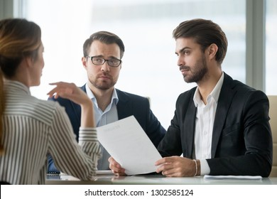 Skeptical male hr managers unconvinced about hiring female candidate, doubtful company recruiters feel uncertain listen to applicant at job interview, bad impression, gender discrimination concept