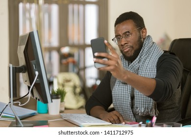 Skeptical professional man in a creative office using his mobile device