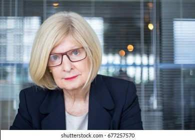 Skeptical senior businesswoman looking at camera