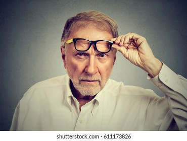 Skeptical senior man with glasses looking at you isolated on gray background. Human emotions, body language