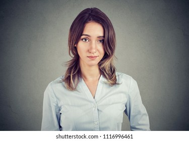 skeptical suspicious young business woman looking at camera isolated on gray wall background