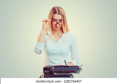 Skeptical woman at typewriter looking at you camera doubtfully isolated on light green yellow background with copy space. Writer having doubts. Skeptically face emotion expression, reaction, feeling
