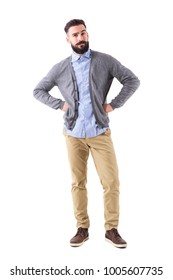 Skeptical young fashionable bearded man with arms on hips looking at camera. Full body length portrait isolated on white studio background.
