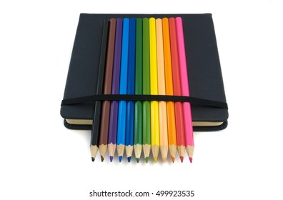 sketch book and colored pencils isolated on white background