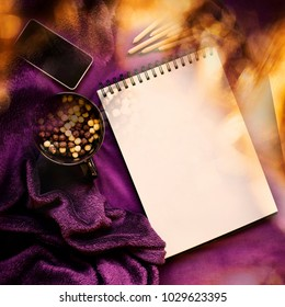 Sketch book, colored pencils, mobile phone, sweets, plaid. Top view. Mock up. Bright purple color, soft warm light and lens flare. Objects for painting, writing and sketching. Concept creation.