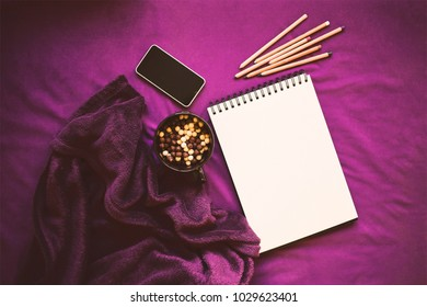 Sketch book, colored pencils, mobile phone, sweets, plaid. Top view. Mock up. Bright purple color, soft warm light. Objects for painting, writing and sketching. Concept creation.