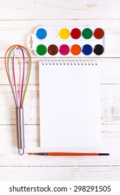 Sketch pad with paints, brush, whisk and tablet. Concept of creativity. Desktop workplace designer, artist, painter. Modern trend template for advertising, mockup, layout, template, banner.