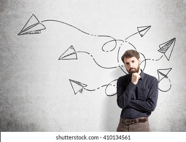 Sketch of paper planes going in different directions on concrete wall and businessman standing next to it