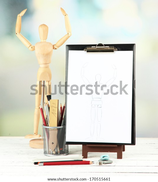 Sketch with professional art materials, on wooden table