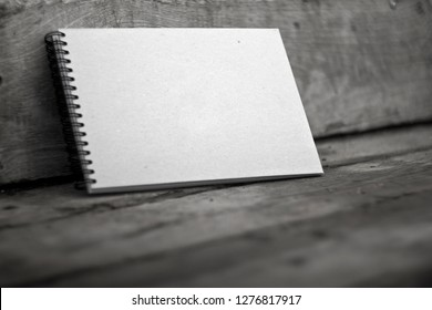 Sketchbook with a hard cardboard cover on a dark wooden background. Close-up.