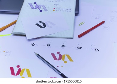 Sketches and drawings of the logo printed on paper. Development of logo design in the studio on a table with a laptop