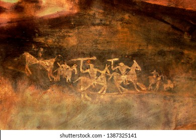 Sketches of warriors on horseback with swords in their hands drawn by primitive people at Bhimbetka Caves near Bhopal, Madhya Pradesh, India, Asia