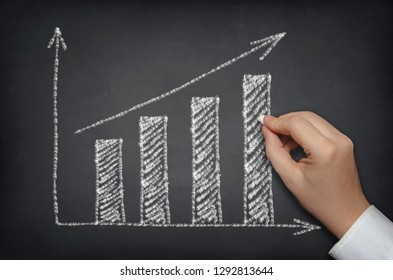 Sketching growth chart on blackboard. Business concept.