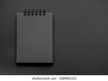A sketchpad with black pages on a black background