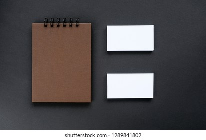 A sketchpad with brown pages and empty business cards on a black background