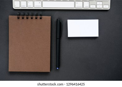 A sketchpad with brown pages, a keyboard and empty business cards on a black background