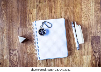 Sketchpad, pen, pencils and small compass on wooden background. Wish list blank. Search for purpose in life. My goals list. An essential question or searching for purpose.