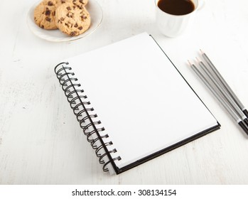 Sketchpad, pencils on the white table, with coffee and chocolate chip cookies on the back