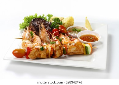 Skewered Chicken meat kebab Barbecue on wooden stick & Grilled Tiger Prawns & Beef Fillet Steak with Sauce & Lemon with Roasted Potato on White Square Plate on White Background. Menu Set, Front View.