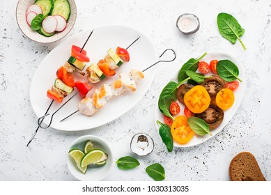 Skewers with chicken fillet, capsicum, zucchini, champignons and fresh colored tomatoes, spinach, cucumber, radish Top view