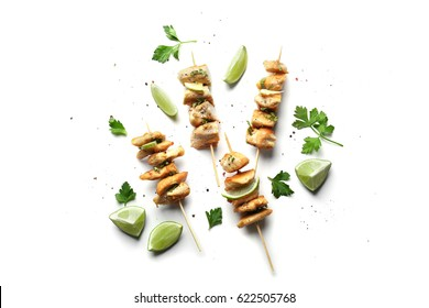 Skewers of delicious tequila lime chicken on white background
