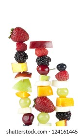 A skewers of fresh mixed fruits isolated on a white surface