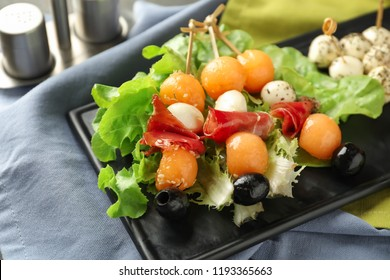Skewers with melon, prosciutto, mozzarella and olives on plate, closeup