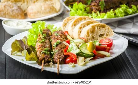 Skewers of minced meat with vegetable salad
